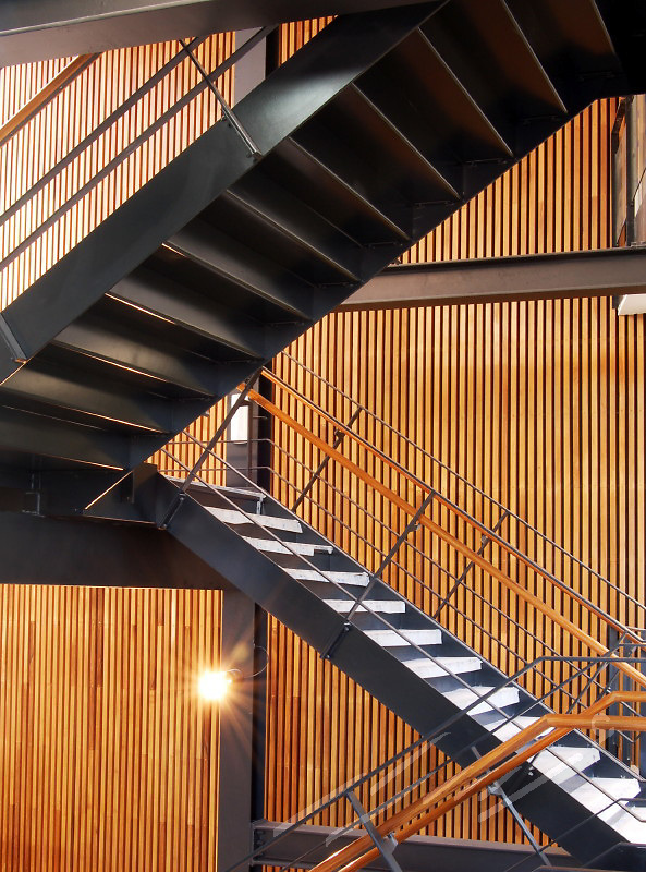 Steel staircase in black, white, and orange hanging in an atrium. Wooden atrium of peach color.