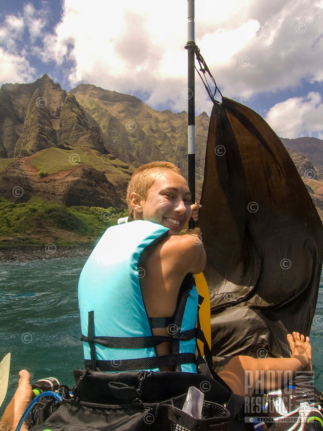 A smiling young woman in a life vest holds onto a makeshift sail on an inflatable kayak off the Na Pali Coast, Kaua'i.