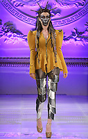 Model walks runway in an outfit from the Kristin Costa Fall 2013 Joan of Arc collection by Kristin Costa, during Couture Fashion Week Fall 2013 in New York, February 17, 2013.