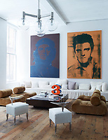 A pair of paintings by Gavin Turk hangs above an Axel Vervoordt sofa in the library; the 1970s suede chairs are by Klaus Uredat, a Robert Indiana sculpture sits atop a vintage French cocktail table and the 1960s chandelier is Austrian; The Philippe Starck chairs in the library were prototypes for the Royalton Hotel and the 18th-century floorboards were salvaged from a Pennsylvania farmhouse.