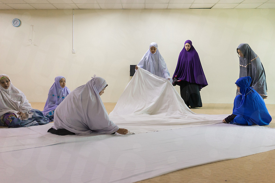 January 10, 2015 - Rawang (Malaysia). Dr. Azlina Jamaluddin (wearing a purple dress) prepare the company's praying room for the Maghrib prayer. Dentist at the Global Ikhwan Clinic in Rawang, she was one of the Obedient Wives Club Organiser. Educated in Australia she joined the company in 2001. © Thomas Cristofoletti / Ruom