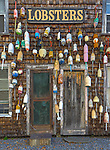 Central Coast; Maine:<br /> Weathered doors and wall covered with lobster buoys