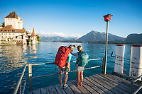 Two women traveling in Switzerland, waiting for the Thunersee Ferry at the Oberhofen dock.