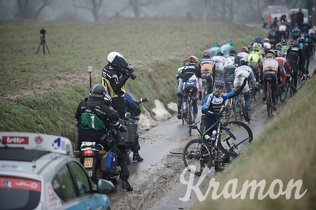 Dwars Door Vlaanderen 2013.Russell Downing (GBR) with a mechanical after a crash on the muddy Ladeuze descent. Jack Bauer (NZL) crashed heavily right in front of him and stays down motionless (at first)