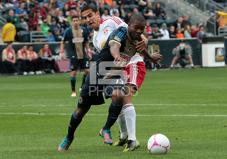 CHESTER, PA - OCTOBER 27, 2012:  Michael Lahoud (13) of the Philadelphia Union is held by  Tim Cahill (17) of the New York Red Bulls during an MLS match at PPL Park in Chester, PA. on October 27. Red Bulls won 3-0.