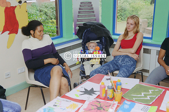 Two women with baby taking part in counselling session at women's shelter,