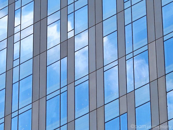 Geometric pattern and reflections in side of building.