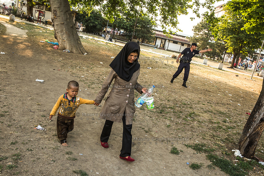 Migranti nel parco della stazione dei bus di Belgrado. Migrants on the bus station park in Belgrade Beograd<br /> Donna velata e figlio. sullo sfondo un poliziotto . Veiled woman and child  . in the background a cop