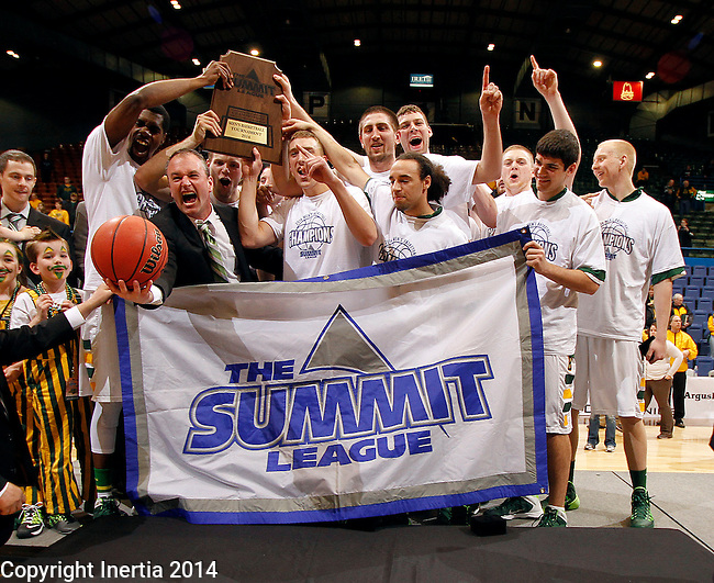SIOUX FALLS, SD - MARCH 11:  Head coach Saul Phillips, left, from North Dakota State University holds the game ball while celebrating with his team following their 60-57 win over IPFW at the 2014 Summit League Men's Basketball Championship Tuesday evening at the Sioux Falls Arena.  (Photo by Dave Eggen/Inertia)