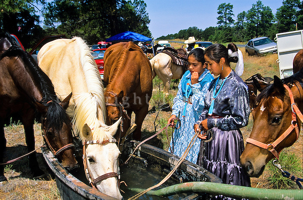 "Navajo girls in traditional dress water their horses while participating in ""Water Is Life Ride"" across the Navajo Nation, Defiance Plateau, Arizona, AGPix_0630."