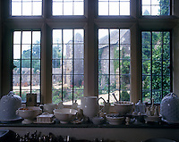 Crockery is stored on the sill of the mullion window in the kitchen