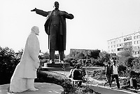 Kazakhstan. Semipalatinsk. A young couple seat on a bench, another couple walks on an alley in a public park near Lenin's statues from the former Soviet Union. Vladimir Ilyich Lenin ( born Vladimir Ilyich Ulyanov. April 22 [O.S. April 10] 1870  - January 21, 1924), was a Russian revolutionary, a communist politician, the main leader of the October Revolution, the first head of the Russian Soviet Socialist Republic and from 1922, the first de facto leader of the Soviet Union. Semey is the kazak name for Semipalatinsk and is located in the Eastern Kazakhstan Province. © 2008 Didier Ruef ...