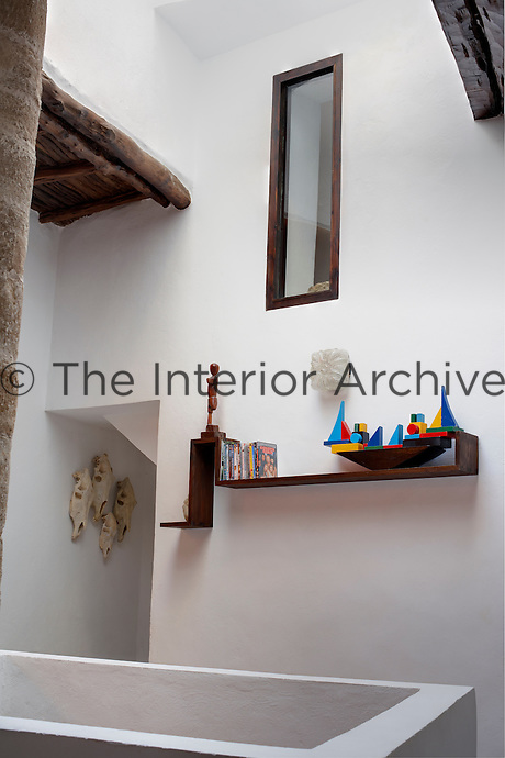 Sculptural open wooden shelving is a feature on the whitewashed walls of the villa