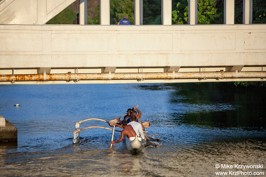 Local Hawaiian men paddling a canoe on Anahulu Stream under the bridge in Haleiwa, Oahu, Hawaii