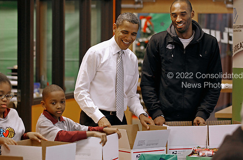 United States President Barack Obama (C) and Los Angeles Lakers guard Kobe Bryant help children volunteers fill care packages during a NBA Cares service event at the Boys and Girls Club at THEARC,   December 13, 2010 in Washington, DC. Bryant and all the members of the 2010 NBA Championship Lakers team volunteered on projects at the club before being honored by the president for their victory. .Credit: Chip Somodevilla - Pool via CNP
