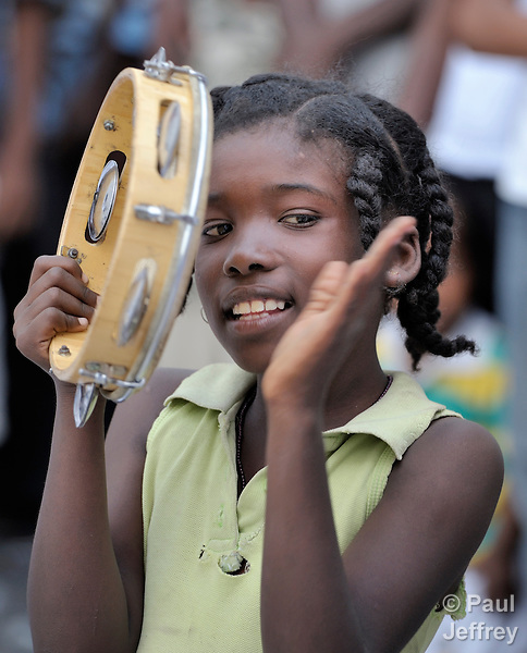 A girl practices plays th tambourine during a capoeira session on January 24 in a camp for homeless families in the Belair section of Port-au-Prince. The program, run by Viva Rio, a Brazilian nongovernmental organization, is designed to help children affected by the quake recover their emotional well-being.
