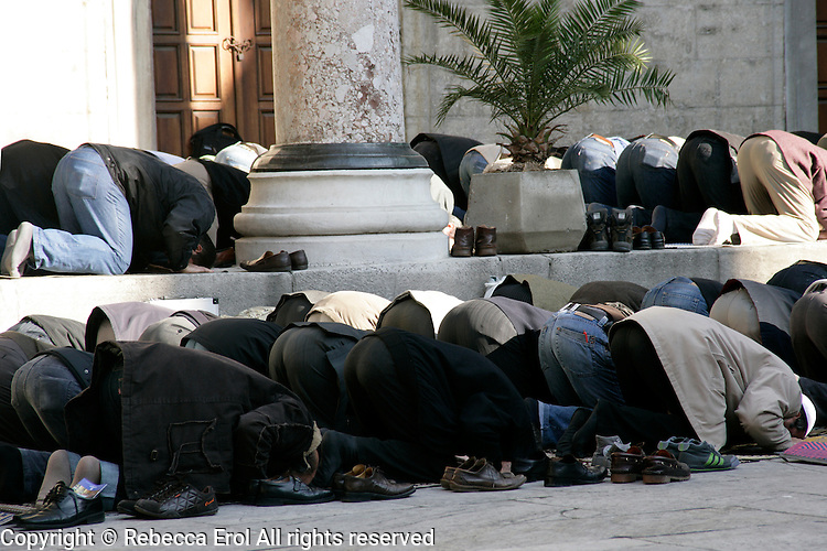 Men praying in the courtyard of the New Mosque, Istanbul, Turkey