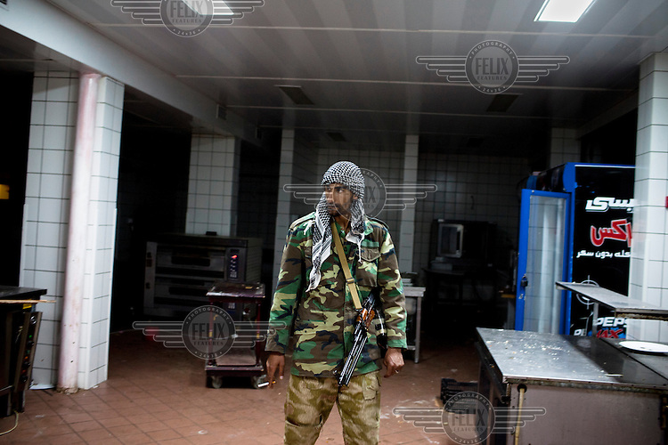 A rebel fighter stands with a gun in a hotel that was vanadalised by Gaddafi's forces the day rebels took back Ras Lanuf. On 17 February 2011 Libya saw the beginnings of a revolution against the 41 year regime of Col Muammar Gaddafi.