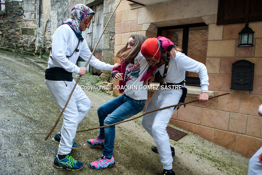 Two Mamuxarros simulate the kidnapping of a young girl during the carnival Unanua in Navarra