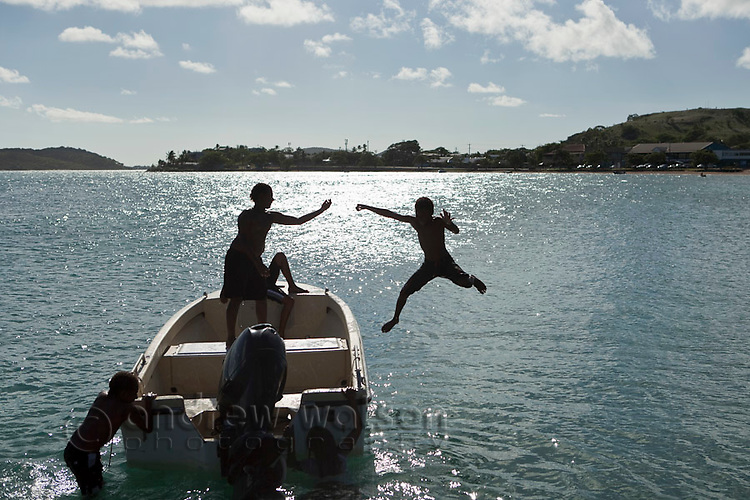Kids leaping off a boat into the waters off Thursday Island, Torres Strait Islands, Queensland, Australia