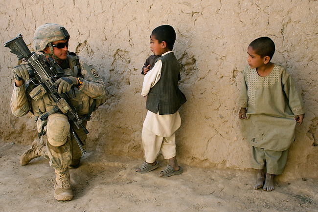 An Afghan boy tries to communicate in the local Pashto language to Pfc. Buddy Moon, as other soldiers with Company C, 2nd Battalion, 508th Parachute Infantry Regiment search for a reported Taliban weapons cache in the village of Jelewar in the Arghandab valley near Kandahar, Afghanistan. Afghan children frequently pester U.S. troops for pens, gum, candy and other small items. April 4, 2010. DREW BROWN/STARS AND STRIPES