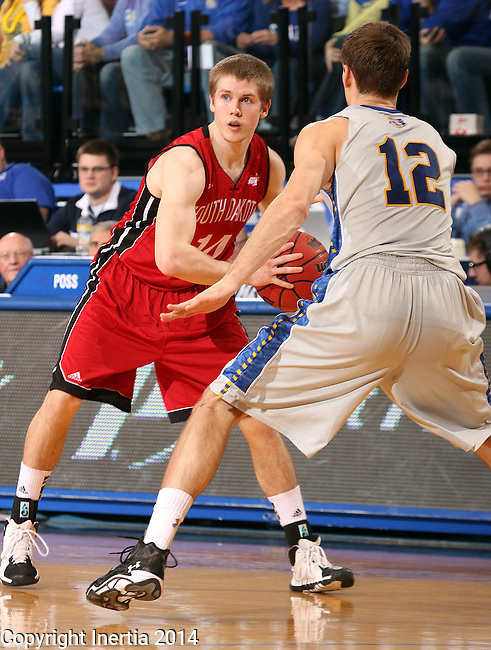 BROOKINGS, SD - MARCH 1:  Casey Kasperbauer #14 from the University of South Dakota looks for a teammate while being pressured by Brayden Carlson #12 from South Dakota State University in the first half or their game Saturday afternoon at Frost Arena in Brookings. (Photo by Dave Eggen/Inertia)
