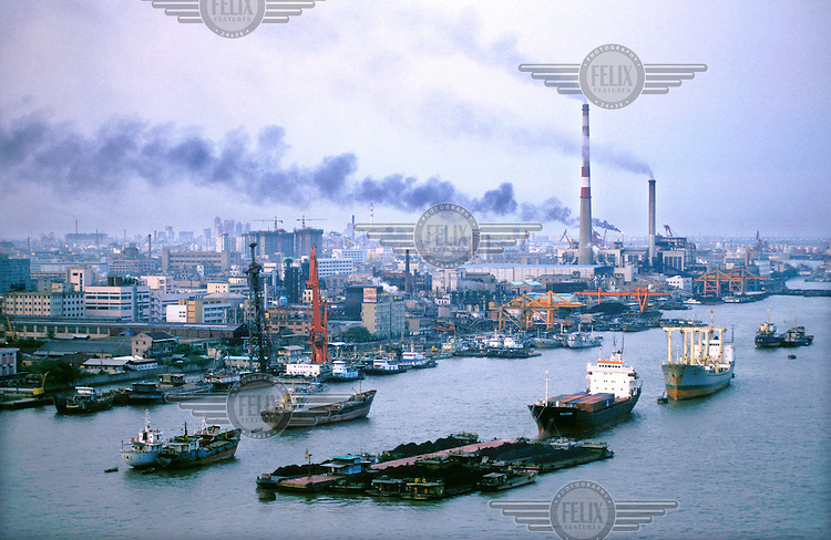 Mark Henley/Panos Pictures..China, Shanghai..Polluting factories next to Huangpu River, with ships and barges holding holding coal.