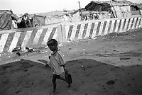 Boy walking in a shanty town in Mumbai, Indai. January 2000