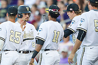 Vanderbilt Commodores outfielder Rhett Wiseman (8) is greeted by his teammates after scoring against the TCU Horned Frogs in Game 12 of the NCAA College World Series on June 19, 2015 at TD Ameritrade Park in Omaha, Nebraska. The Commodores defeated TCU 7-1. (Andrew Woolley/Four Seam Images)
