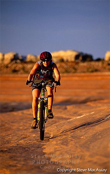 Female mountain biker riding in the golden light of the setting sun, Bartlett Wash, Moab, Utah
