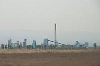 Daytime landscape view of a commercial factory building site with a smokestack near Dàtóng Shì Chéng Qū in Shānxī Province, China  © LAN