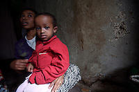 Tlbech, 27 years old, and her son Zarhiun, 4, both HIV positive talk about their recent health problems in their small house in one of the poorest neighborhoods in Addis Ababa, ethiopia on Monday June 05 2006..Talbech and Zarihun live on a 180 birr ( 20 USD ) per month sponsorship from the HfC NGO. they spend 100 Birr for rent leaving less than 10 USD for food and other necessities. Nevertheless they are a privileged family in the country..Tlbech besides fighting againt the virus and taking care of her child provides home base care assistance in Addis to other HIV patients in need..Ethiopia is one of the countries most affected by HIV/AIDS. Of its population of 77 million, three million are HIV-positive, according to government statistics. Every day sees 1,000 new infections. A million children under 14 have lost one or both parents to AIDS, and 200,000 children are living with AIDS. That makes Ethiopia the country with the most HIV-positive children.