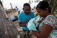 Eleições 2014.<br /> Sandoval Mendes Lima, 43 anos, casado pai de 5 filhos entrega o caçula para sua esposa após a saída do barco.<br /> Ribeirinhos chegam de canoas, rabetas e barcos a 76 zona eleitoral sessão 257 na ilha Grande logo após a entrega das urnas por funcionários do TRE/Pará. 271 eleitores<br /> Belém, Pará, Brasil.<br /> Foto Paulo Santos<br /> 05/10/2014