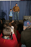 Thursday March 2, 2006  Anchorage, Alaska  Race fans take a photo of musher Jim Lanier and his son as Jim tells the crowd his chosen starting number at the musher's pre-race drawing and banquet, the largest banquet in Alaska at the Eagan Center.