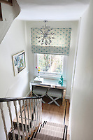 Black lines continue from the staircase runner onto the floorboards of the landing. A blue and white variation on the cushion coveres has been used for the blind