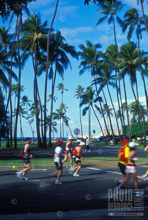 Runners with palms in back ground near Kapiolani Park at the Honolulu Marathon