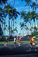 Runners with palms in back ground near Kapiolani Park at the Honolulu Marathon