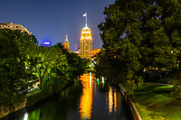 San Antonio Tower Life Building - San Antonio images on prints, canvas and metal. We capture this view of the Tower Life building looking up the riverwalk at night.  You can see the buildings reflections in the water. The Tower Life Building is a landmark and historic building in Downtown San Antonio, Texas.  The Tower Life building is a major part of the San Antonio skyline with it masses flag pole it can't be missed. The Tower building was completed in 1929 it was 403 feet at the time. In 2010 it was renovated and a copper top was place on it with a 100 ft flag pole attached to the top as in the orginal design. The 30 story, eight sided, neo-gothic, brick and terracotta structure is an easily recognizable landmark with its gargoyle rain spouts, green patina copper top and flag pole. The Tower Life building was first occupied by Sears but has been owned by many businesses since it completion in 1929 today it is owned by Tower Life Insurance company.  The builiding was placed on the National Register of Historic Places in 1991.