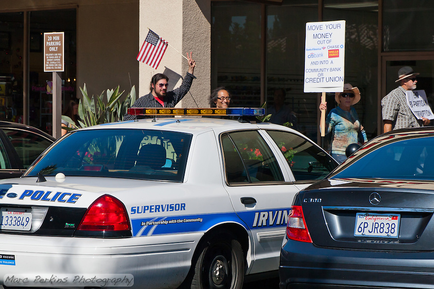 Sia flashes a peace sign while marching in front of an Irvine police supervisor's car during the Saturday November 5 Occupy Orange County, Irvine march.  Dean is walking next to him.