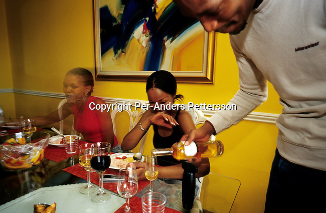 Eric Mogaki, a partner in a construction company, serves desert wine to friends that were invited for a brunch to his house on December 26, 2003 in a southern suburb in Johannesburg, South Africa. Eric and his family belong to a growing middle-class in the country, now owning houses, cars, and their children attend a former white private school. The number of affluent blacks has increased steadily the fall of Apartheid and the start of democracy in the country in 1994. (Photo by: Per-Anders Pettersson)..