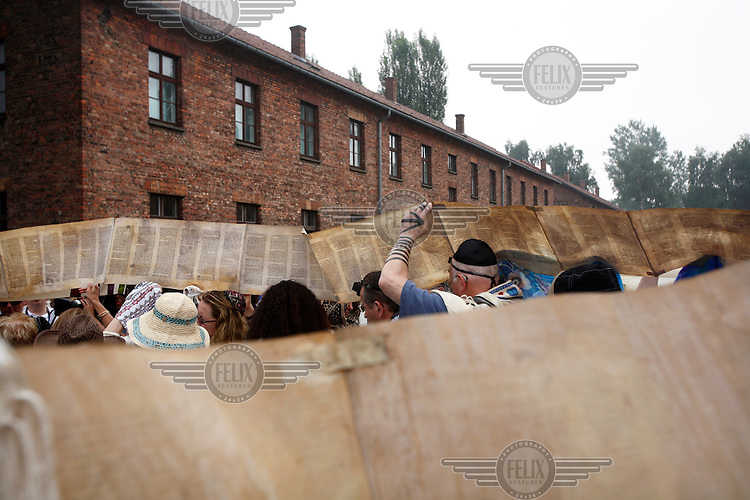 On a visit to the Auschwitz (Birkenau) former Nazi concentration camp organised by the Taube Foundation, Jewish cantors hold up an unwound Torah during the prayer for the dead. It is estimated that between 1.1 and 1.5 million Jews, Poles, gypsies and others were killed here in the Holocaust between 1940-1945.