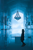 Sweden, SWE, Kiruna, 2006-Apr-12: A woman walking through a long corridor in the Jukkasjarvi icehotel with table and lustre made of ice.