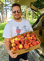 Westside Eagle Observer/RANDY MOLL Jamon Abercrombie, of Lees Summit, Mo., shows a box of peaches he and his family picked on Saturday at Taylor's Orchard in Gentry. The orchard is now open for those who wish to purchase peaches or pick them.