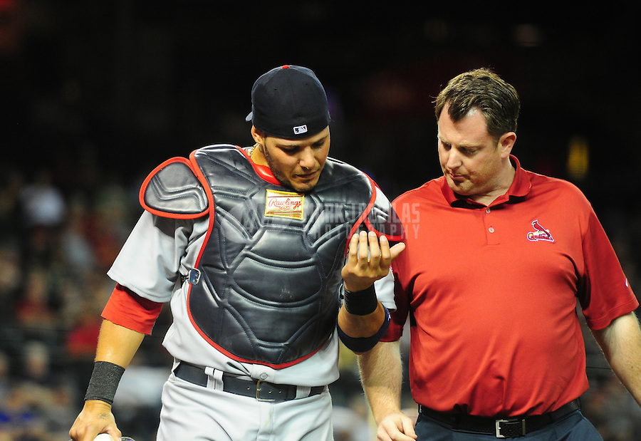 May 8, 2012; Phoenix, AZ, USA; St. Louis Cardinals catcher Yadier Molina (left) leaves the game with a trainer after being injured in the ninth inning against the Arizona Diamondbacks at Chase Field. Mandatory Credit: Mark J. Rebilas-