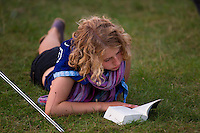 Girl reading a book in the grass in the evening on the first day. Photo: Magnus Fröderberg/Scouterna
