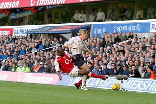 13 November 2004: Arsenal defender Lauren tackles Erik Edman of Spurs during the Premiership match between Tottenham Hotspur and Arsenal. Arsenal won the game played at White Hart Lane 5-4. Photo: Action Plus..041113 soccer football premier league premiership player players footballer footballers