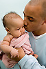 Father giving a kiss to his baby daughter whilst towling her dry,