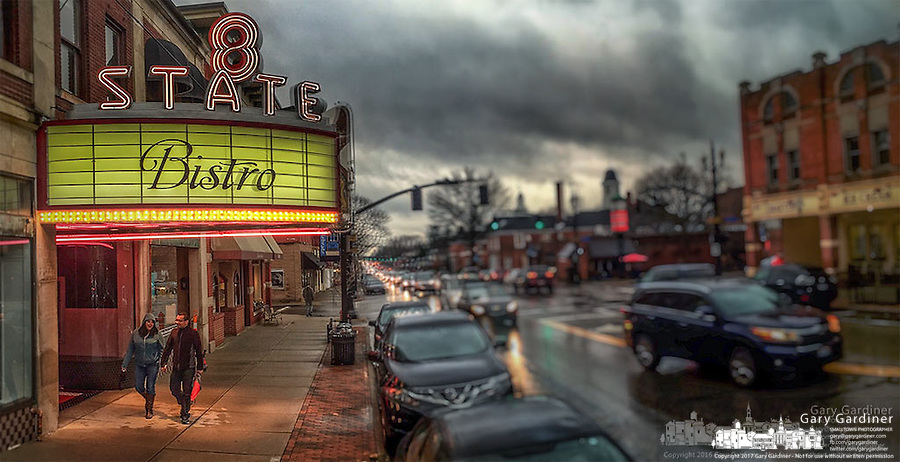 A coupole walks beneath the restored State Theater marquee where it is converted to an upscale restaurant in Westerville, Ohio.