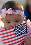 Three-month-old Natalissa Arambul looks at a U.S. flag as the USS John C. Stennis, a 1,092-foot-long aircraft carrier, pulls into it's homeport on July 10, 2009 at Naval Station Kitsap in Bremerton, WA.  The carrier and it's 3,200 crewmembers arrived Friday after spending a six-month deployment in support of  Middle East operations. She was born while her father, Petty Officer Third Class Gilbert Arambul was at sea. (© Jim Bryant Photo. All Rights Reserved