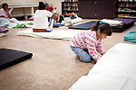 Seven-year-old Davina Tafoya prepares to sleep on the floor of a multipurpose room at Stockton's Shelter for the Homeless, July 18, 2012. With some of the highest rates of unemployment and home foreclosures in the country, Stockton is grappling with large numbers of homeless.